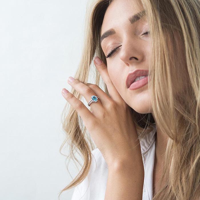 Золотое родированное кольцо Лейла в белом цвете с голубым топазом и белыми фианитами 000082337